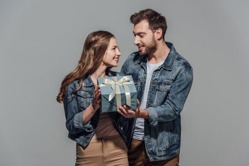 Όμορφο ευτυχές νέο κιβώτιο δώρων εκμετάλλευσης ζευγών και χαμόγελο του ενός τον άλλον στοκ φωτογραφία με δικαίωμα ελεύθερης χρήσης