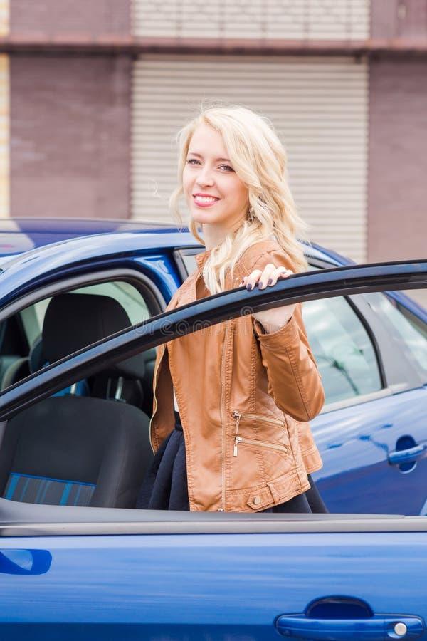 Όμορφο ευτυχές νέο κορίτσι που στέκεται κοντά στο αυτοκίνητό της στοκ εικόνα με δικαίωμα ελεύθερης χρήσης
