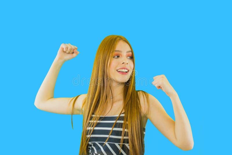 Όμορφο ευχαριστημένο χαρούμενο και ευτυχές κορίτσι που κραυγάζει με τα όπλα που αυξάνονται στοκ φωτογραφία