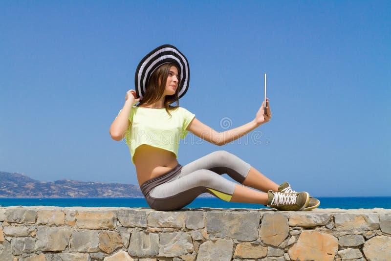 Όμορφο εφηβικό brunette χρησιμοποιώντας μια ταμπλέτα από στοκ εικόνα με δικαίωμα ελεύθερης χρήσης