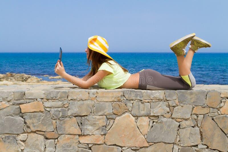 Όμορφο εφηβικό brunette χρησιμοποιώντας μια ταμπλέτα από στοκ φωτογραφία με δικαίωμα ελεύθερης χρήσης
