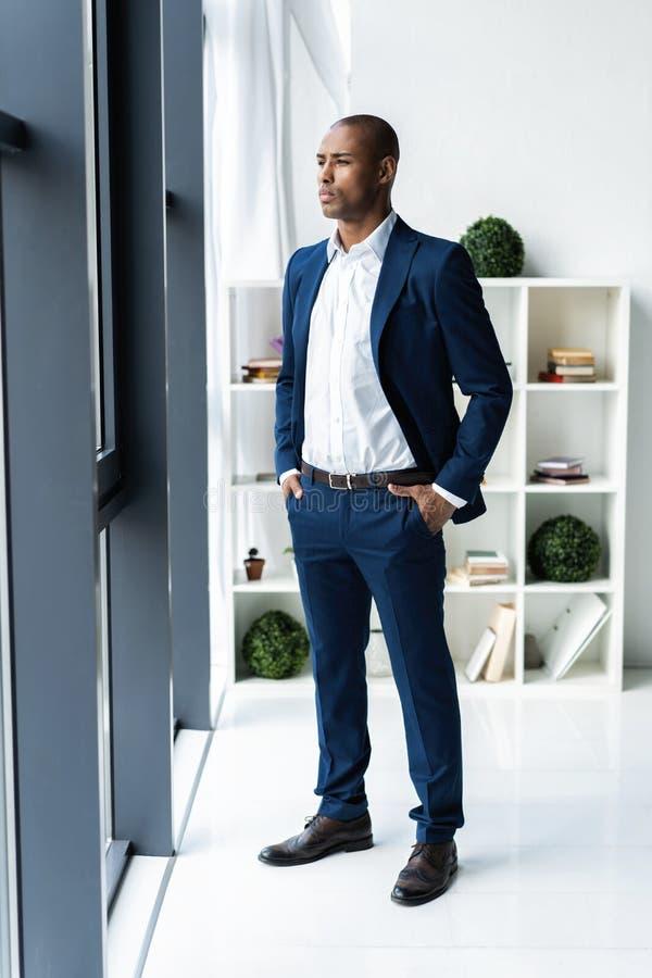 Όμορφο εύθυμο εκτελεστικό επιχειρησιακό άτομο αφροαμερικάνων στο γραφείο χώρου εργασίας στοκ φωτογραφία