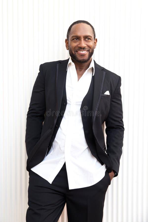 Όμορφο εύθυμο επιχειρησιακό άτομο αφροαμερικάνων στο αριστοκρατικό μαύρο κοστούμι στοκ φωτογραφία