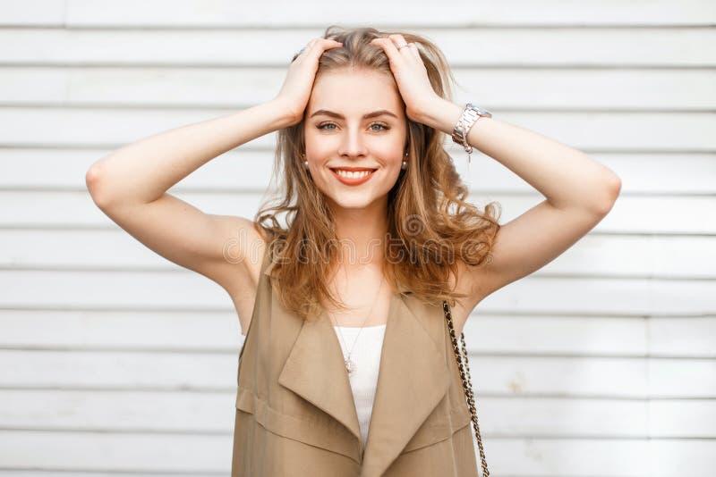 Όμορφο εύθυμο κορίτσι που χαμογελά και που απολαμβάνει κοντά σε έναν ξύλινο τοίχο στοκ εικόνα