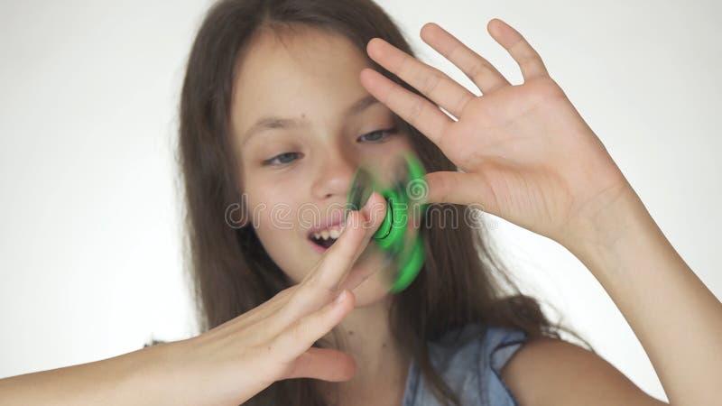 Όμορφο εύθυμο παιχνίδι κοριτσιών εφήβων με τον πράσινο fidget κλώστη στο άσπρο υπόβαθρο στοκ εικόνες
