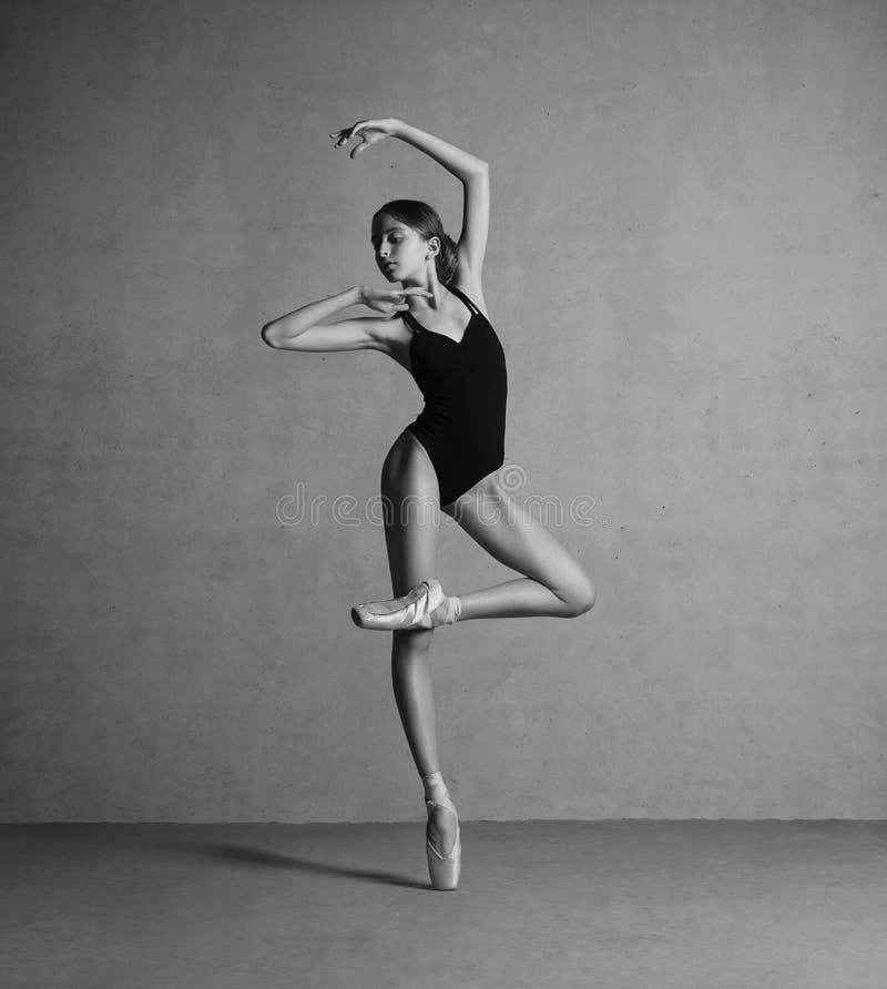 Όμορφο εύκαμπτο ballerina που χορεύει μαύρο σε swimmwear στοκ εικόνα
