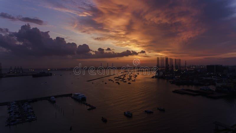 Όμορφο, ζαλίζοντας ηλιοβασίλεμα πέρα από το νερό, πέρα από τις βάρκες σε μια βιομηχανικό αποβάθρα ή έναν λιμένα κοιτάγματος στοκ εικόνες με δικαίωμα ελεύθερης χρήσης