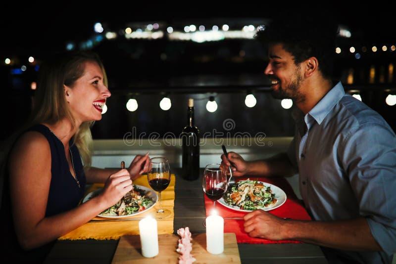 Όμορφο ζεύγος ερωτευμένο έχοντας το ρομαντικό γεύμα τη νύχτα στοκ εικόνες