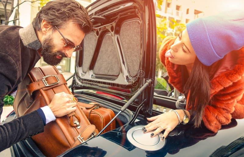 Όμορφο ζεύγος μόδας που πηγαίνει στις διακοπές, που φορτώνουν το αυτοκίνητό τους στοκ φωτογραφία