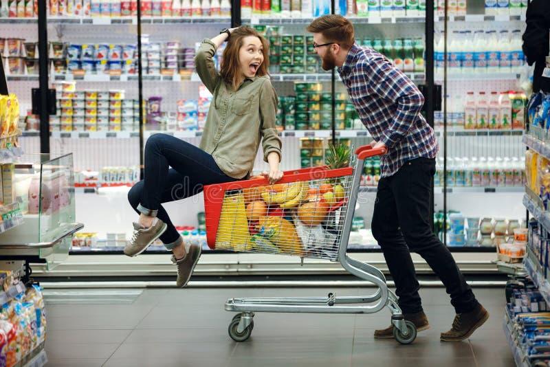 Όμορφο ζεύγος που έχει τη διασκέδαση επιλέγοντας τα τρόφιμα στην υπεραγορά στοκ φωτογραφία