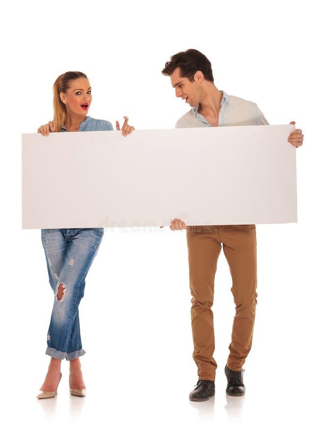Όμορφο ζεύγος που κρατά ένα κενό άσπρο σημάδι στοκ φωτογραφία
