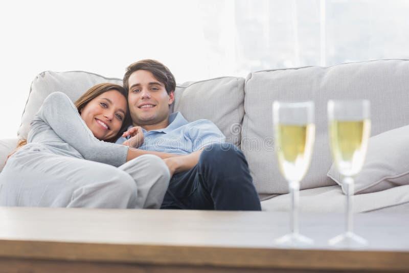 Όμορφο ζεύγος που στηρίζεται σε έναν καναπέ με τα φλάουτα της σαμπάνιας στοκ εικόνα με δικαίωμα ελεύθερης χρήσης