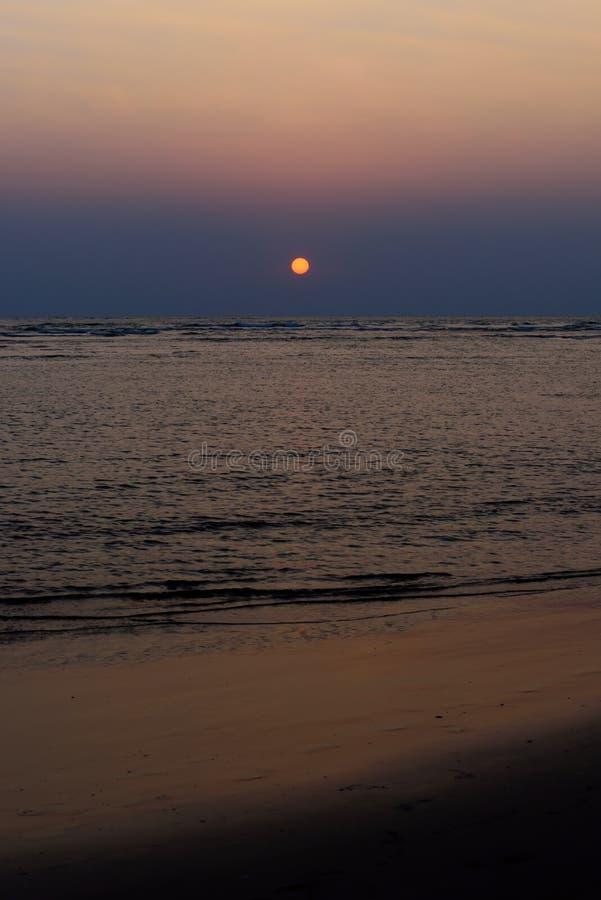Όμορφο ζωηρόχρωμο ηλιοβασίλεμα στην ωκεάνια, κάθετη φωτογραφία Παραλία άμμου, τα σύνολα ήλιων στα σύννεφα επάνω από τη θάλασσα στοκ εικόνες