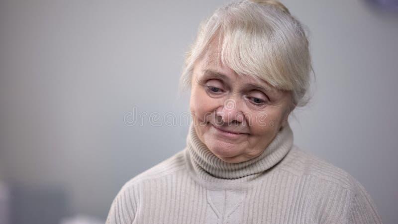 Όμορφο ηλικιωμένο χαμόγελο γυναικών εύκολα, που θυμάται τις προηγούμενες ημέρες, μνήμες ευχαρίστησης στοκ εικόνα με δικαίωμα ελεύθερης χρήσης