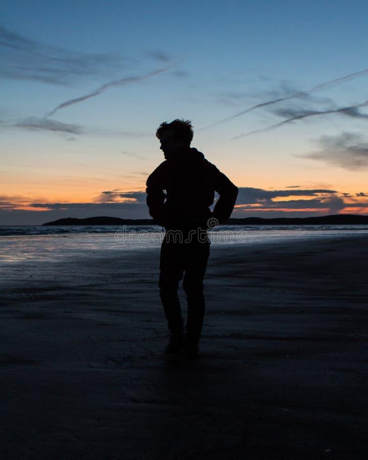 Όμορφο ηλιοβασίλεμα με έναν σκιαγραφημένο χαρακτήρα στοκ φωτογραφία