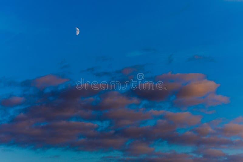 Όμορφο ηλιοβασίλεμα με τα πορτοκαλιά σύννεφα, το βαθιούς μπλε ουρανό και το φεγγάρι στοκ φωτογραφία με δικαίωμα ελεύθερης χρήσης