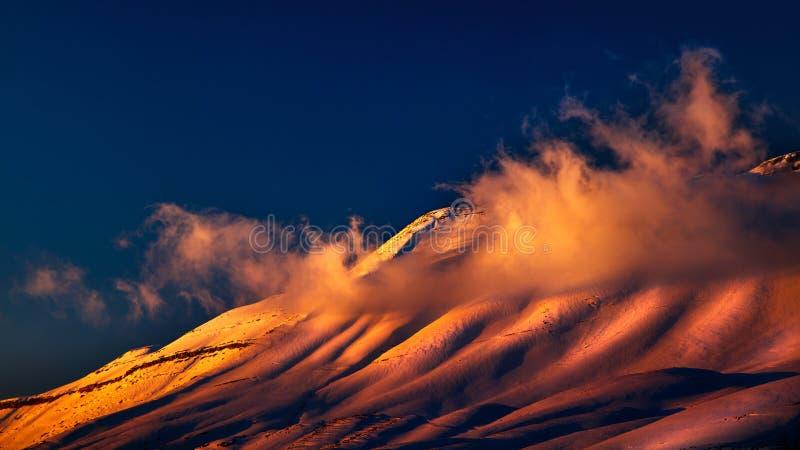 Όμορφο ηλιοβασίλεμα πέρα από τα χιονώδη βουνά στοκ φωτογραφίες
