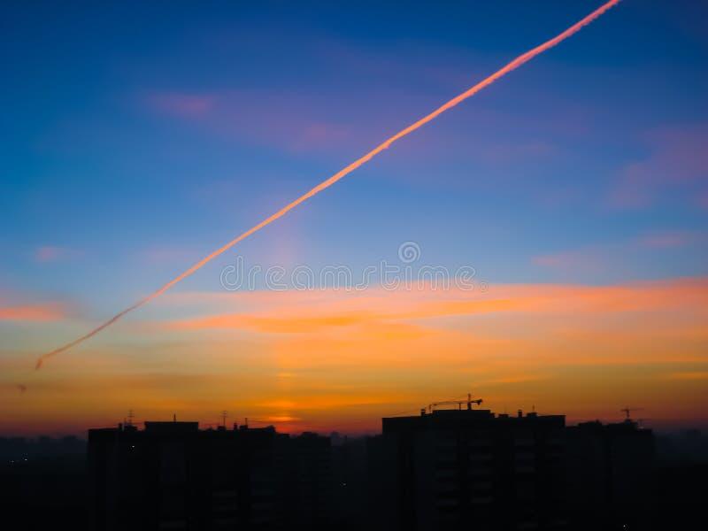 Όμορφο ηλιοβασίλεμα πέρα από την πόλη με ένα ίχνος από το αεριωθούμενο αεροπλάνο στοκ εικόνα