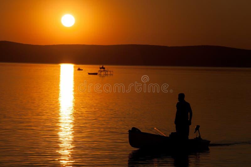 Όμορφο ηλιοβασίλεμα πέρα από τη λίμνη Balaton με τις σκιαγραφίες ψαράδων ` στοκ εικόνες