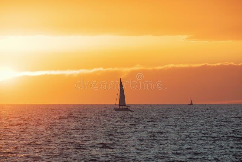 Όμορφο ηλιοβασίλεμα στη θάλασσα με την πλέοντας βάρκα στοκ εικόνες