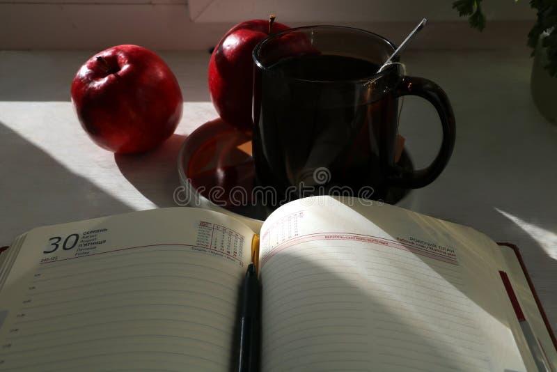Όμορφο ημερολόγιο στον ξύλινο πίνακα στην ηλιόλουστη ημέρα και το μήλο δύο και το φλυτζάνι του κρύου τσαγιού Το μεγάλο σχέδιό μου στοκ φωτογραφία με δικαίωμα ελεύθερης χρήσης