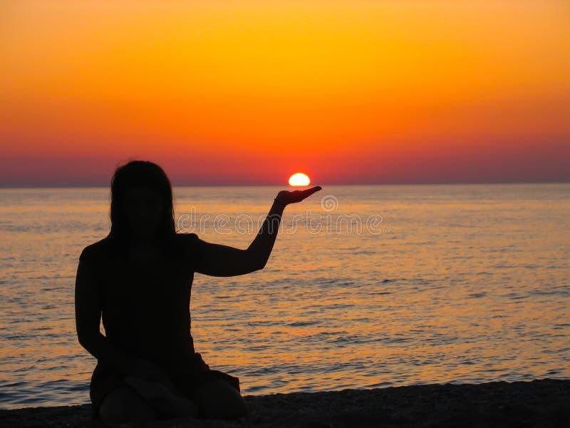 Όμορφο ηλιοβασίλεμα με τη σκιαγραφία ενός κοριτσιού που κρατά τον ήλιο στοκ εικόνες