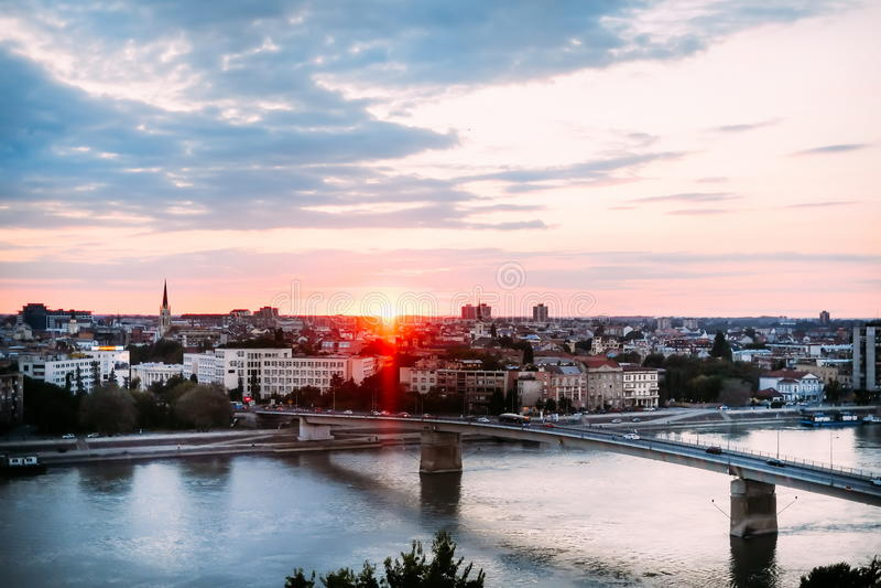 Όμορφο ηλιοβασίλεμα πέρα από τον ποταμό Δούναβη και την πόλη του Νόβι Σαντ με τη γέφυρα ουράνιων τόξων στοκ φωτογραφίες