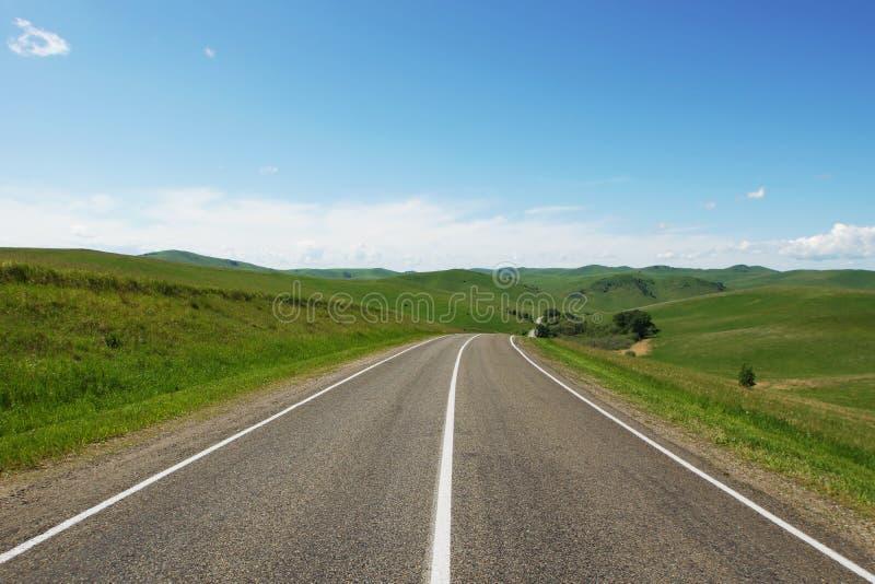 Όμορφο θερινό τοπίο με έναν ευθύ αυτοκινητόδρομο ασφάλτου που πηγαίνει μεταξύ των πράσινων λόφων στοκ εικόνα