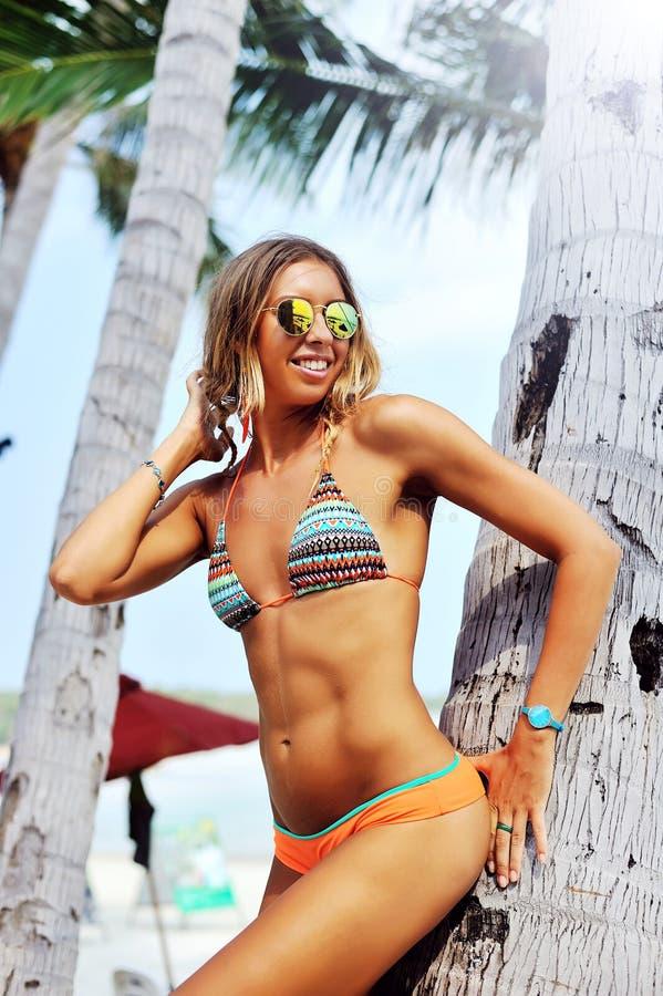 Όμορφο θηλυκό πρότυπο που θέτει σε μια παραλία κοντά τους φοίνικες στοκ εικόνα με δικαίωμα ελεύθερης χρήσης