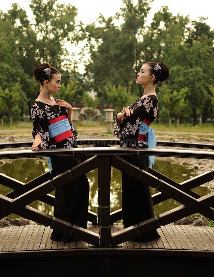 Όμορφο ιαπωνικό κορίτσι γυναικών με το διπλάσιό της στο κιμονό garde στοκ φωτογραφία