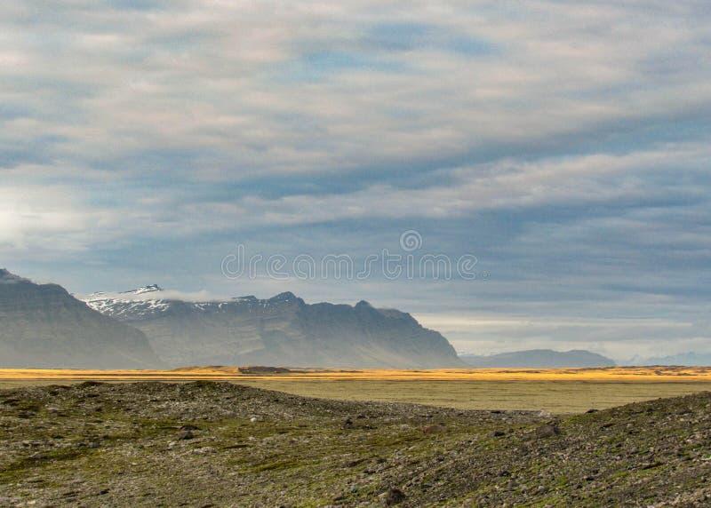Όμορφο ισλανδικό τοπίο με τον ουρανό ηλιοβασιλέματος και βουνά στο υπόβαθρο στη νότια Ισλανδία, Ευρώπη στοκ εικόνες