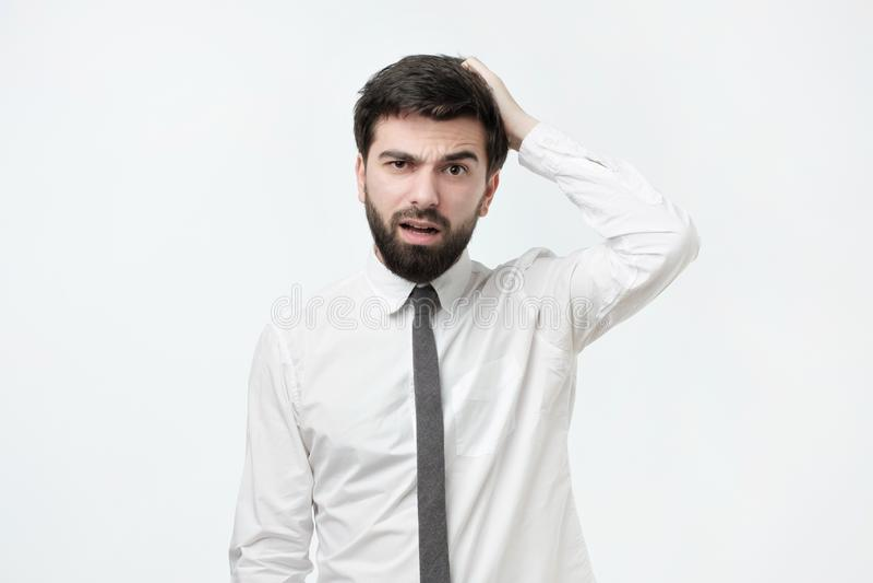 Όμορφο ισπανικό άτομο με το γρατσουνίζοντας κεφάλι γενειάδων μπερδεμένος ή ανίδεος στοκ φωτογραφία