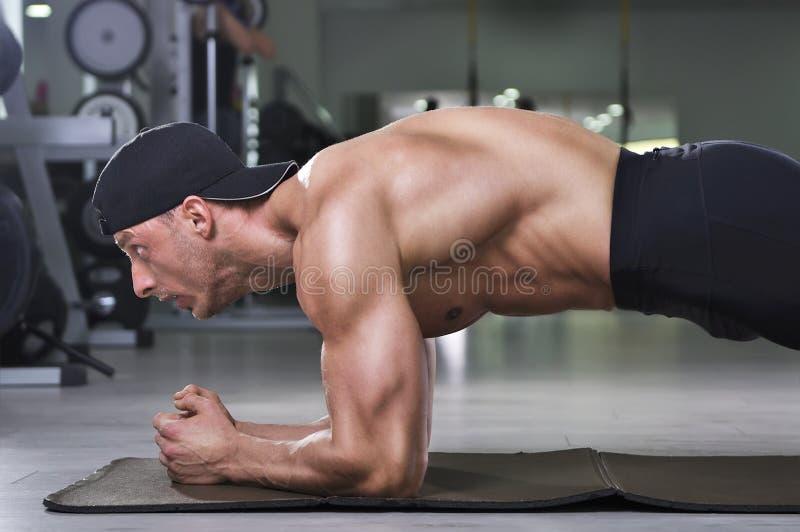Όμορφο ισχυρό αθλητικό άτομο που κάνει την άσκηση σανίδων στοκ εικόνες