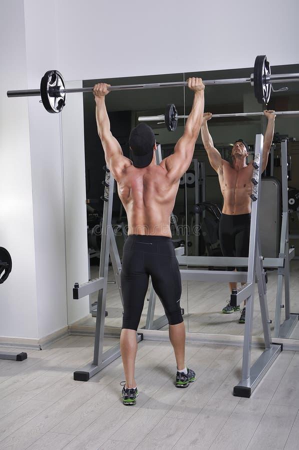 Όμορφο ισχυρό αθλητικό άτομο που κάνει barbell την άσκηση Τύπου ώμων στοκ φωτογραφίες