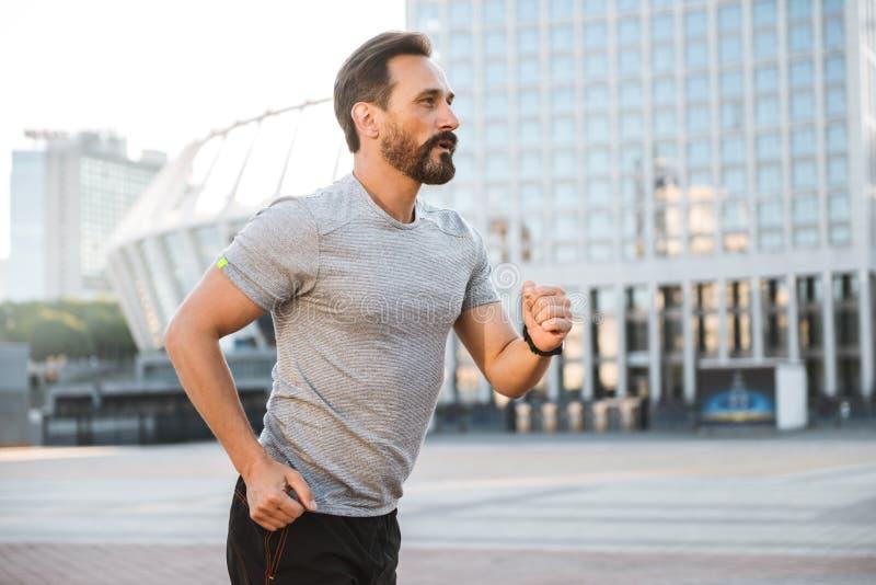 Όμορφο ισχυρό ώριμο τρέξιμο αθλητικών τύπων στοκ εικόνα