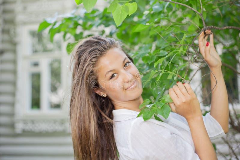 Όμορφο ισχύω κοριτσιών για τον κλάδο με τα φύλλα στοκ εικόνες