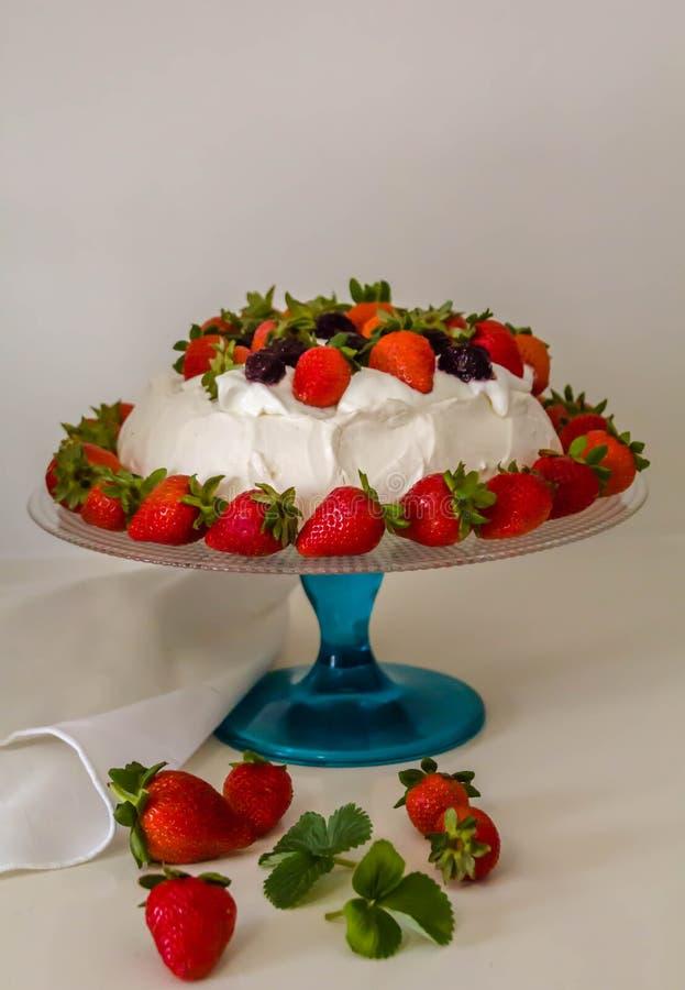 Όμορφο κέικ Pavlova φιαγμένο από γαλλική μαρέγκα, κτυπημένη κρέμα, που διακοσμείται με τη φράουλα στοκ εικόνες
