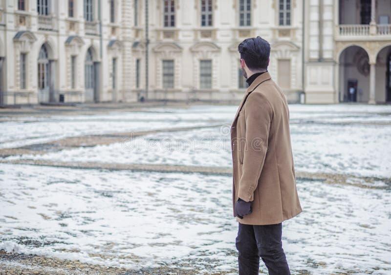 Όμορφο καθιερώνον τη μόδα άτομο στη χιονώδη πόλη στη χειμερινή ημέρα στοκ εικόνες