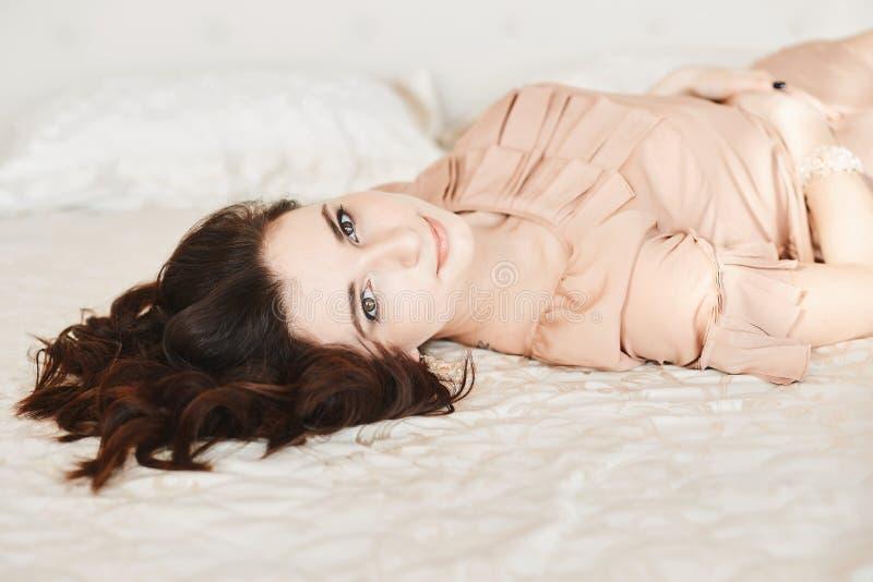 Όμορφο και αισθησιακό πρότυπο κορίτσι brunette με το ευγενές makeup και με το τέλειο δέρμα στην μπεζ τοποθέτηση φορεμάτων στο κρε στοκ εικόνες