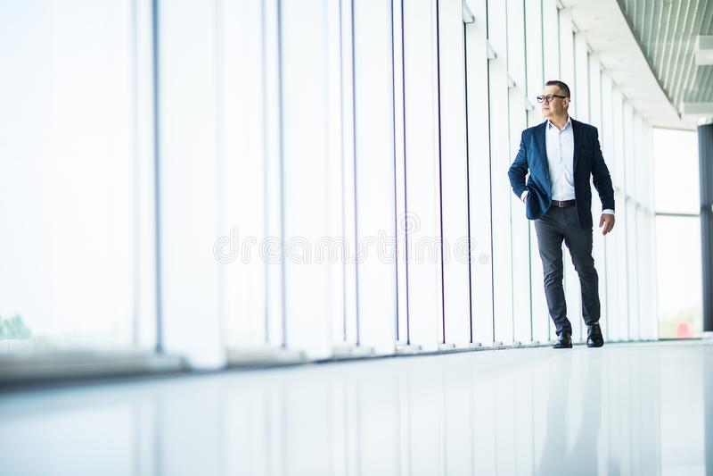 Όμορφο και επιτυχές ανώτερο επιχειρησιακό άτομο που περπατά στο σύγχρονο εσωτερικό γραφείων στοκ εικόνες