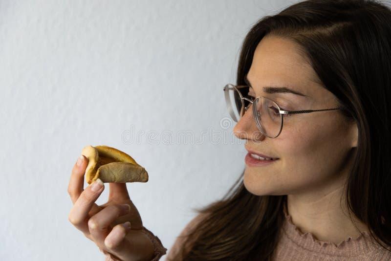Όμορφο και ευτυχές πορτρέτο γυναικών που τρώει hamantash το μπισκότο βερίκοκων Purim στοκ φωτογραφία