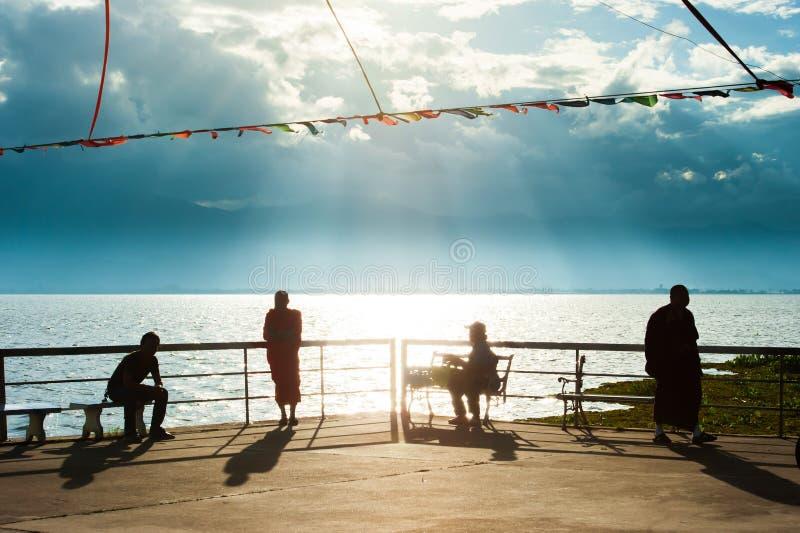 Όμορφο καλοκαίρι, ειρηνικός φυσικός της όχθης της λίμνης στο σούρουπο, βουδιστικοί μοναχοί και άνθρωποι που χαλαρώνουν στο φως ηλ στοκ φωτογραφία
