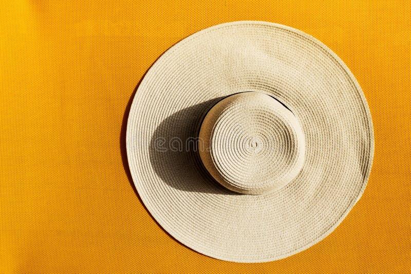 Όμορφο καπέλο αχύρου στο κίτρινο δονούμενο ζωηρό υπόβαθρο Τοπ όψη στοκ εικόνα με δικαίωμα ελεύθερης χρήσης