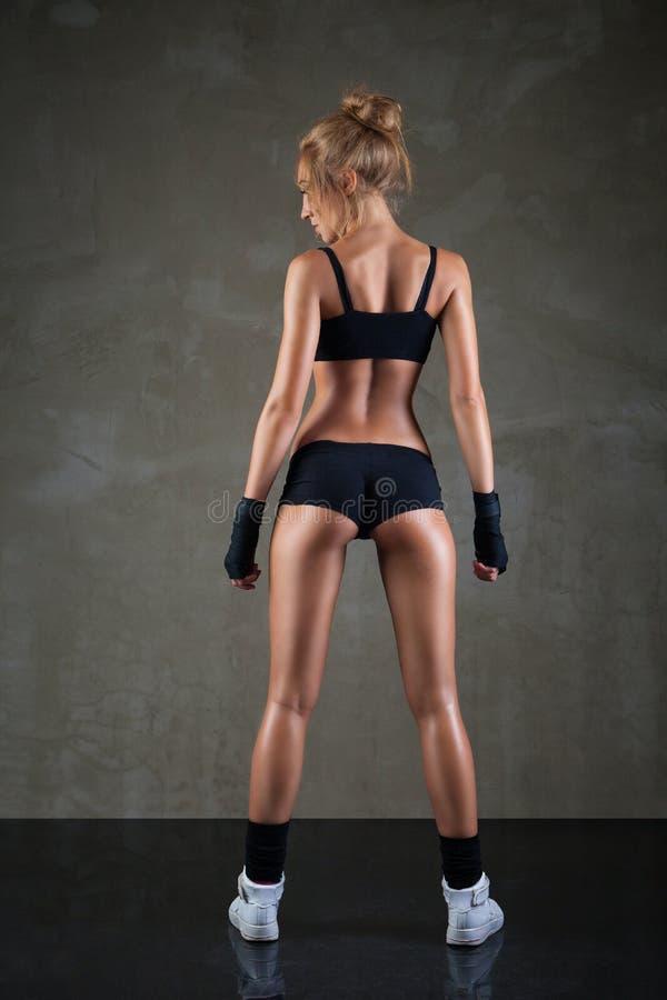 Όμορφο κατάλληλο, προκλητικό θηλυκό σώμα στο σκοτεινό γκρι στοκ εικόνες