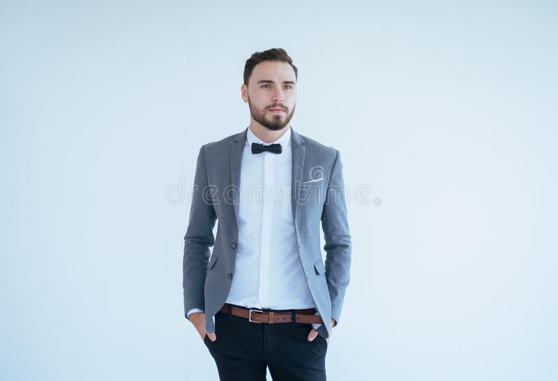 Όμορφο καυκάσιο άτομο με τη γενειάδα στο επίσημο σμόκιν και κοστούμι που στέκεται και που χαμογελά στο άσπρο υπόβαθρο, το διάστημ στοκ φωτογραφία με δικαίωμα ελεύθερης χρήσης