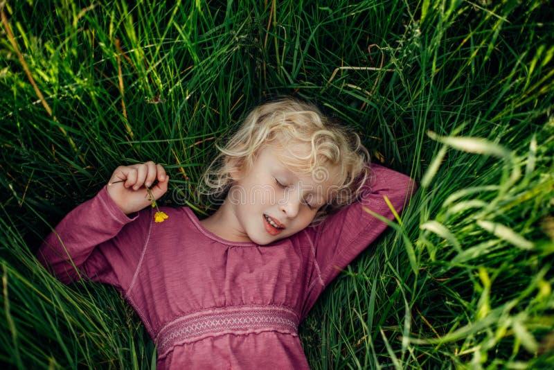Όμορφο καυκάσιο κορίτσι στην ψηλή χλόη στο λιβάδι στο ηλιοβασίλεμα Ύπνος χαμόγελου που ονειρεύεται το καυκάσιο κορίτσι με τις ιδι στοκ εικόνα με δικαίωμα ελεύθερης χρήσης