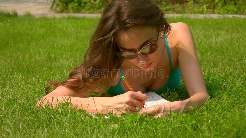 Όμορφο καυκάσιο κορίτσι brunette που βάζει στο χορτοτάπητα και τη colorizing εικόνα στοκ φωτογραφίες με δικαίωμα ελεύθερης χρήσης