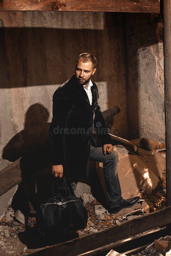 Όμορφο καλά-ντυμένο άτομο στο σακάκι και με την τσάντα στοκ φωτογραφίες