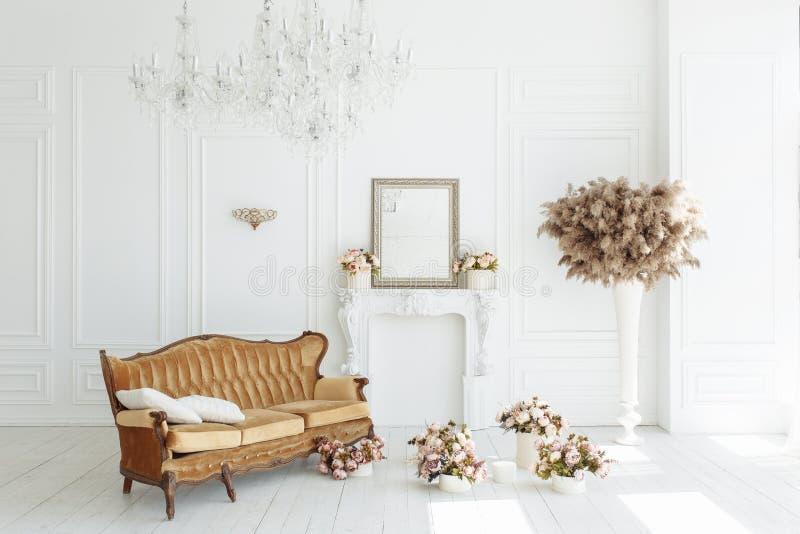 Όμορφο κλασσικό άσπρο εσωτερικό με μια εστία, έναν καφετή καναπέ και έναν εκλεκτής ποιότητας πολυέλαιο Αναδρομικός, κλασικοί οριζ στοκ εικόνες