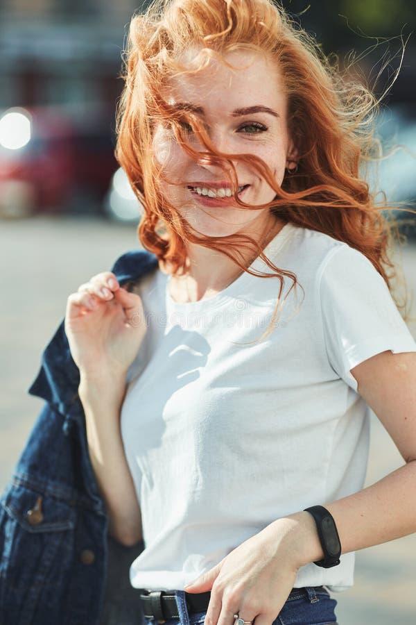Όμορφο κοκκινομάλλες κορίτσι που έχει τη διασκέδαση στην οδό Τα κορίτσια έχουν έναν όμορφο αριθμό, μια άσπρη μπλούζα και τα τζιν  στοκ εικόνες